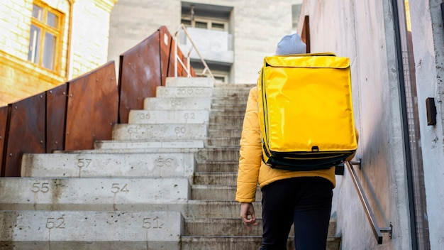 Fattorino in inverno con zaino giallo salire le scale