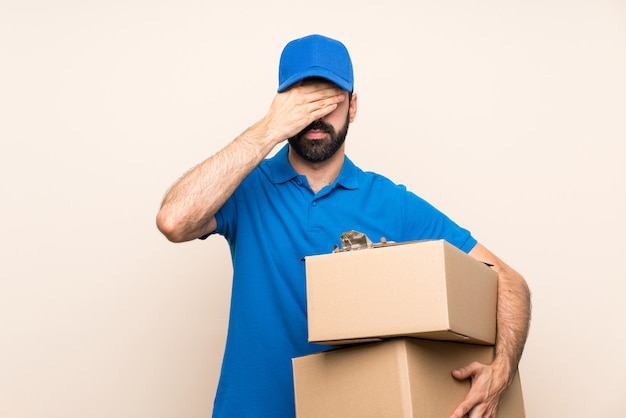 Delivery man with beard   covering eyes by hands. do not want to see something