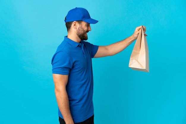 Delivery man with beard isolated on blue wall with happy expression