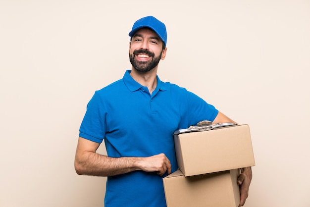 Delivery man with beard over isolated  keeping the arms crossed in frontal position
