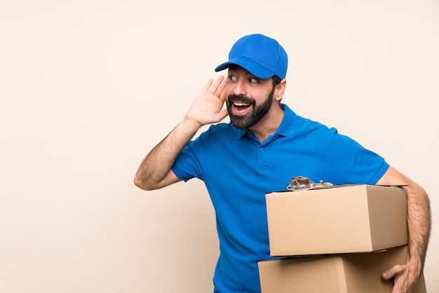 Delivery man with beard over isolated listening to something by putting hand on the ear