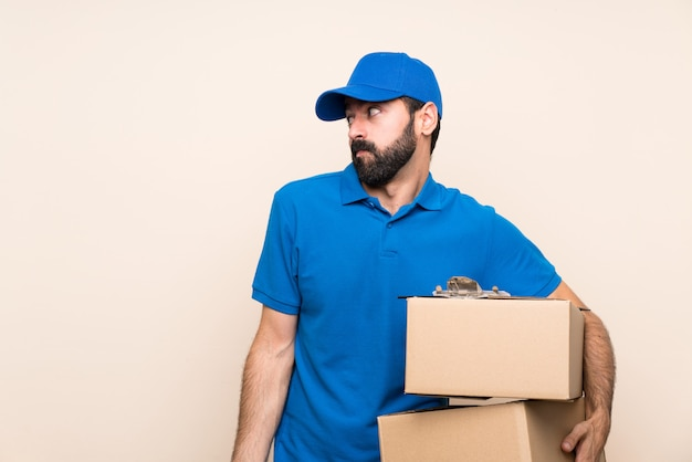 Delivery man with beard over isolated making doubts gesture looking side