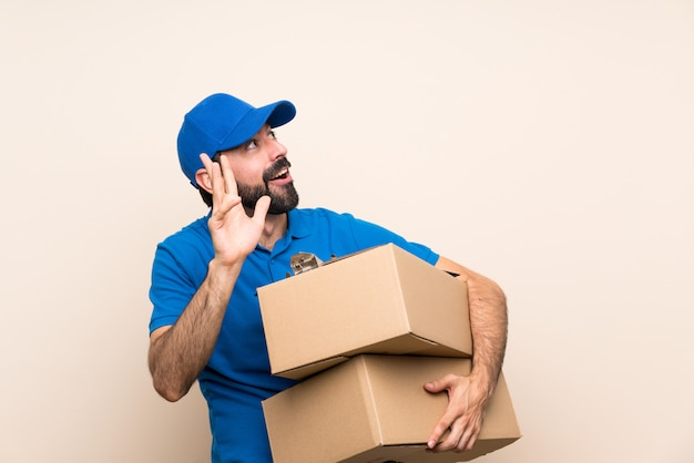 Delivery man with beard over isolated nervous and scared