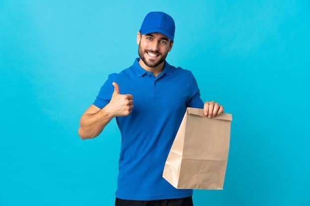 Доставщик с бородой, изолированные на синем фоне с большими пальцами руки вверх, потому что произошло что-то хорошее