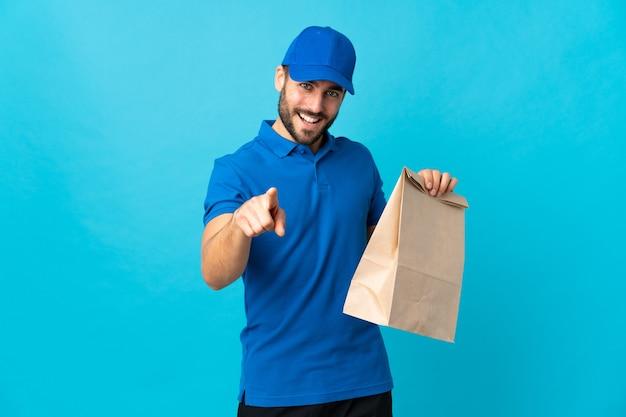 青い壁に孤立したひげを持つ配達人は自信を持ってあなたに指を指しています
