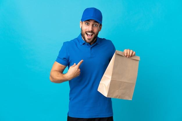 Доставка человек с бородой, изолированные на синей стене с удивленным выражением лица