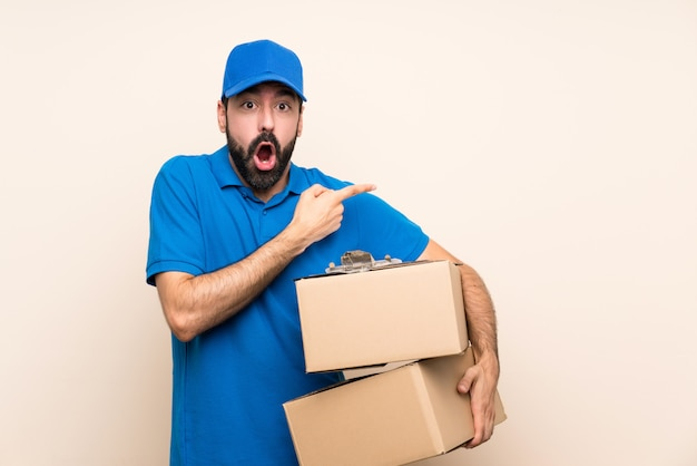 Delivery man with beard over isolated surprised and pointing side