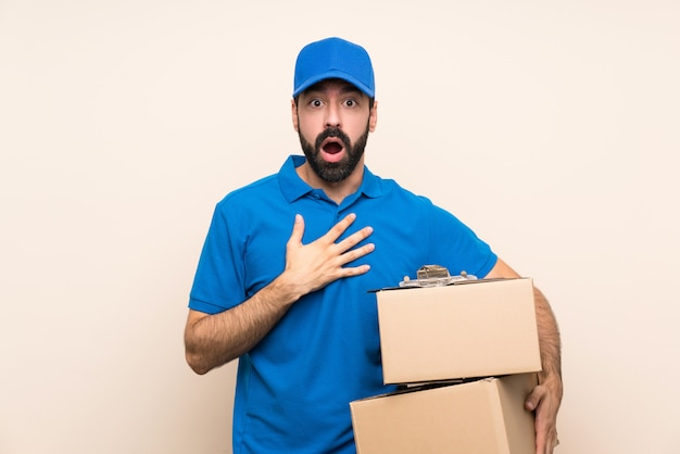 Delivery man with beard over isolated  surprised and shocked while looking right