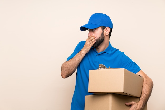 Delivery man with beard over isolated wall covering mouth and looking to the side
