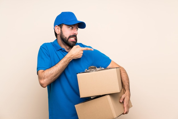 Delivery man with beard over isolated wall frightened and pointing to the side