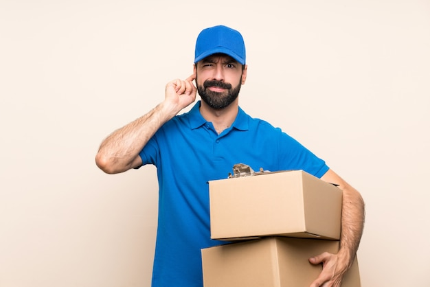 Delivery man with beard over isolated wall frustrated and covering ears
