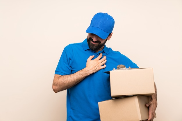Delivery man with beard over isolated wall having a pain in the heart
