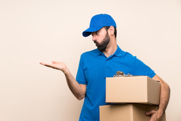 Delivery man with beard over isolated wall holding copyspace with doubts