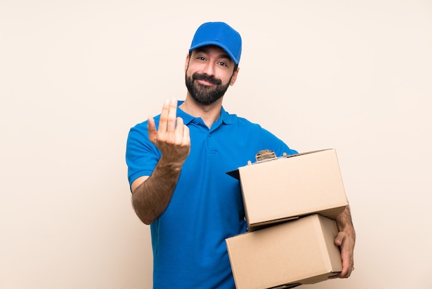 Delivery man with beard over isolated wall inviting to come with hand. happy that you came