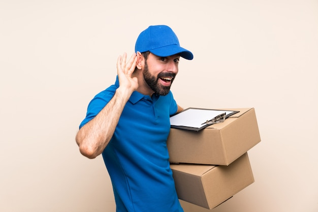 Delivery man with beard over isolated wall listening to something by putting hand on the ear