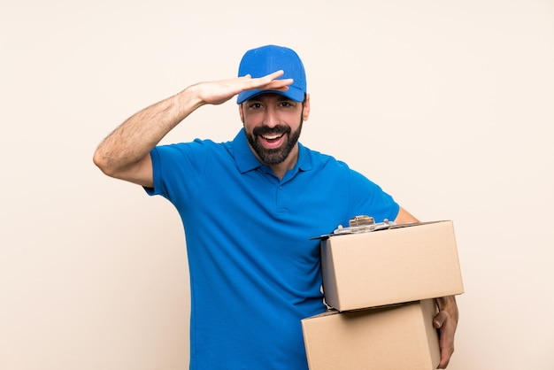 Delivery man with beard over isolated wall looking far away with hand to look something