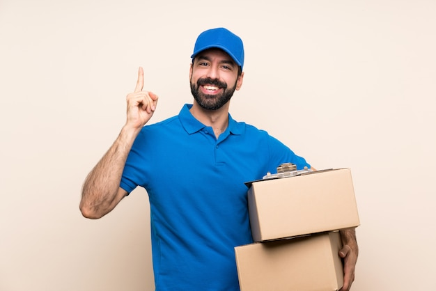 Delivery man with beard over isolated wall pointing up a great idea