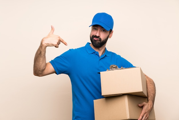 Delivery man with beard over isolated wall proud and self satisfied