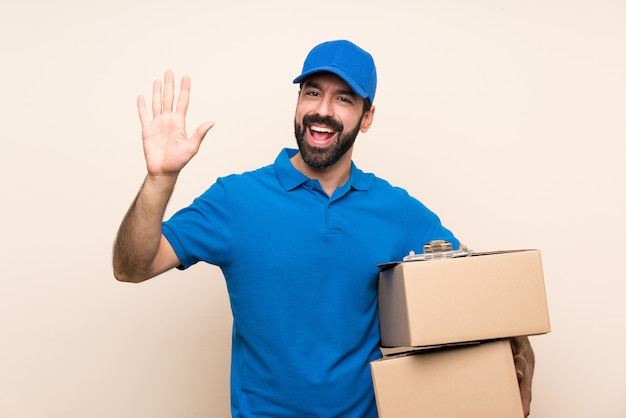 Delivery man with beard over isolated wall saluting with hand with happy expression