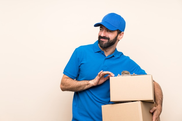 Delivery man with beard over isolated wall scheming something