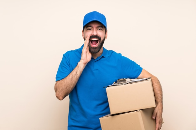 Delivery man with beard over isolated wall shouting and announcing something