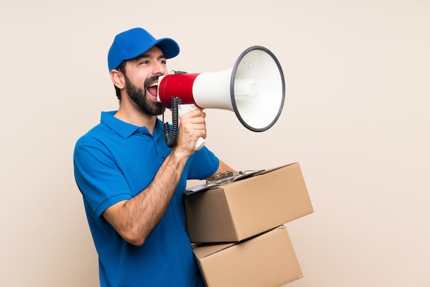 Delivery man with beard over isolated wall shouting through a megaphone