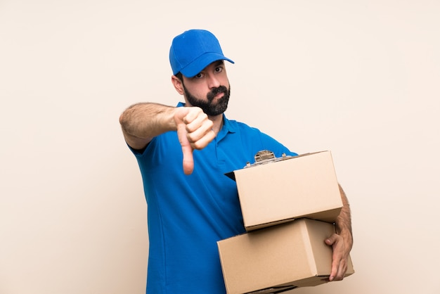 Delivery man with beard over isolated wall showing thumb down with negative expression