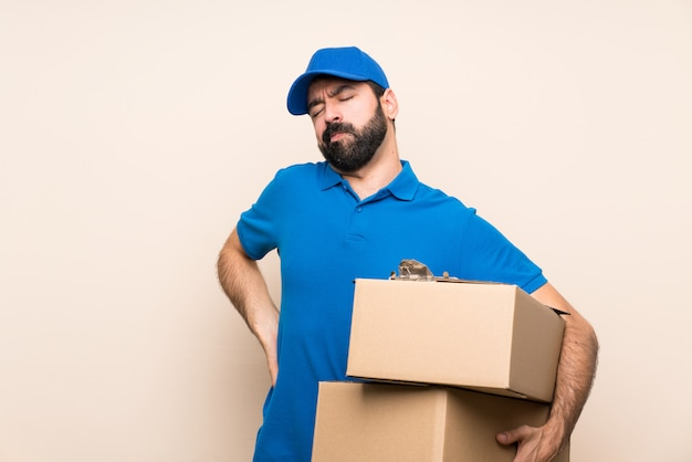 Delivery man with beard over isolated wall suffering from backache for having made an effort
