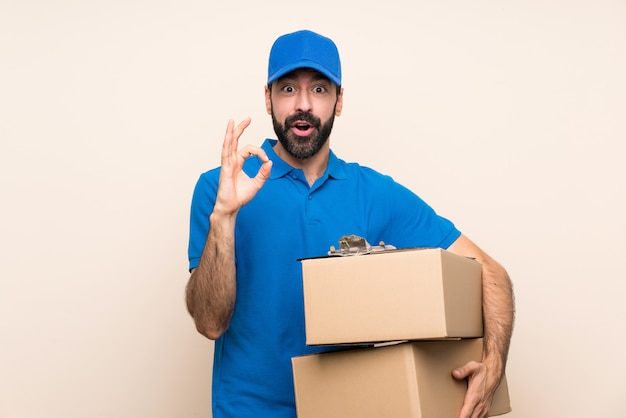 Delivery man with beard over isolated wall surprised and showing ok sign