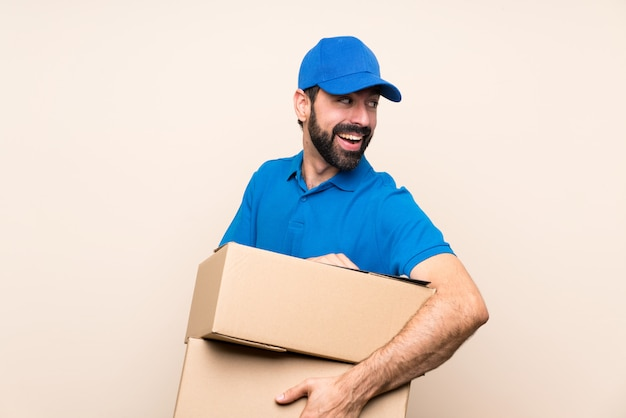 Delivery man with beard over isolated wall with arms crossed and happy