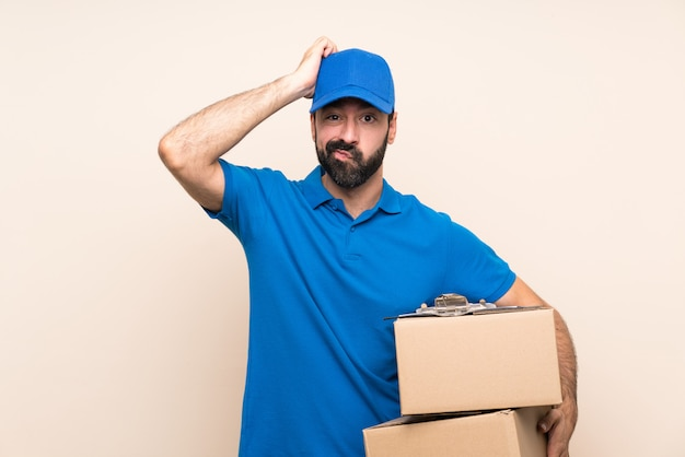 Delivery man with beard over isolated wall with an expression of frustration and not understanding