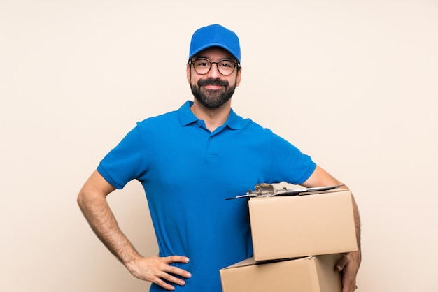 Delivery man with beard over isolated wall with glasses and happy