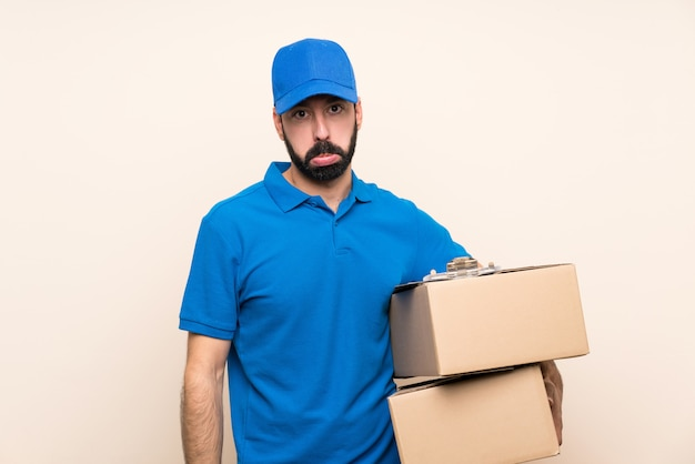 Delivery man with beard over isolated wall with sad and depressed expression