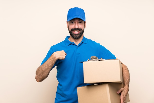 Delivery man with beard over isolated wall with surprise facial expression