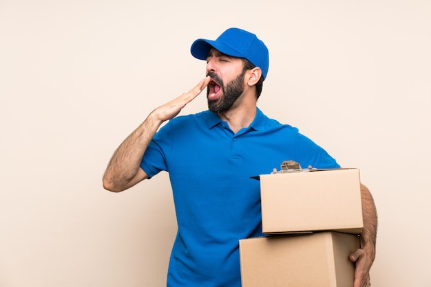 Delivery man with beard over isolated wall yawning and covering wide open mouth with hand