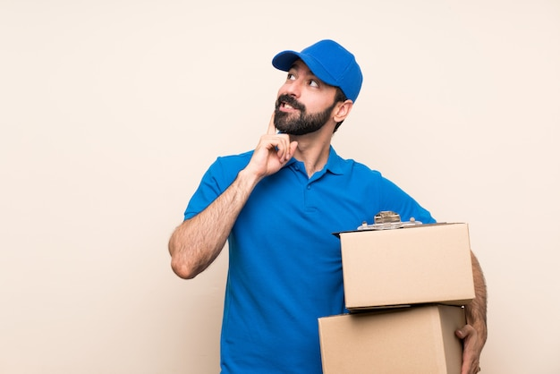 Delivery man with beard   thinking an idea while looking up