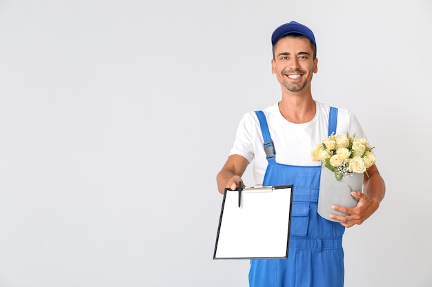 Доставка человек с букетом цветов и буфером обмена на свете