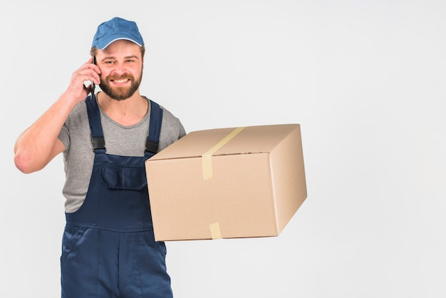 Delivery man with box talking by phone