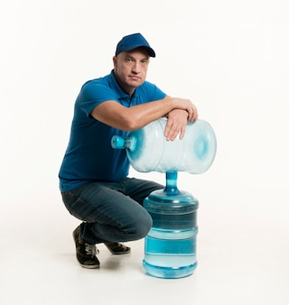 Delivery man with cap posing with water bottles