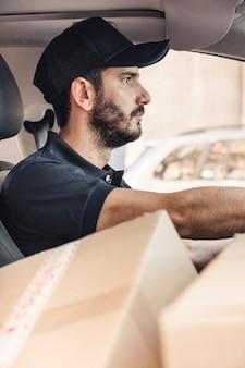 Uomo di consegna con scatole di cartone guida di veicoli