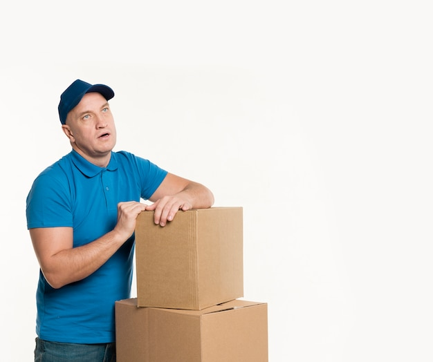 Delivery man with cardboard boxes posing while exhausted