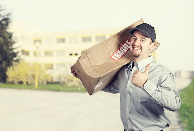 Delivery man with damaged shoulder pack, smiling expression and thumb up