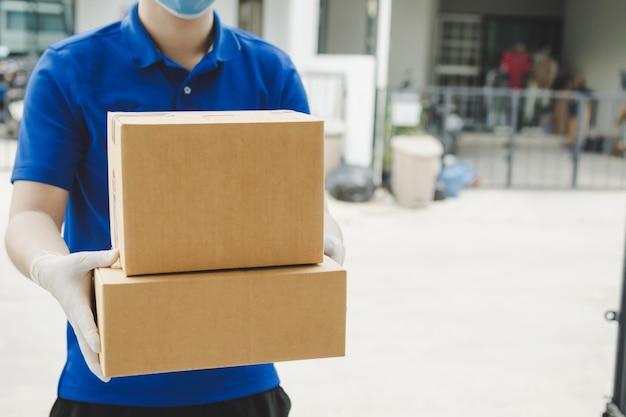 Delivery man with face mask holding boxes