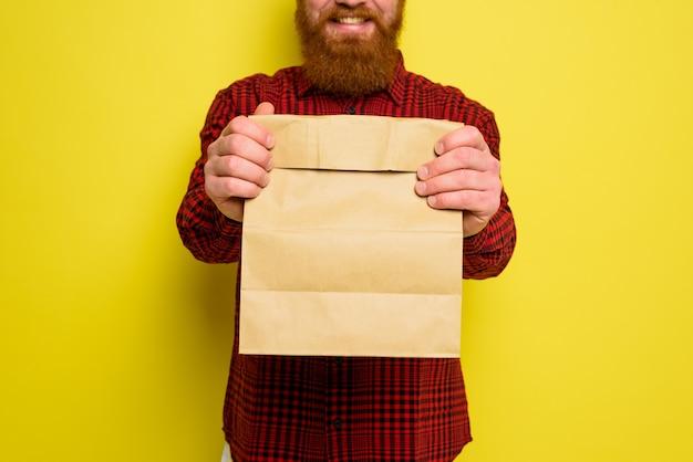 모자와 수염을 가진 배달 남자는 행복한 표정을 가지고