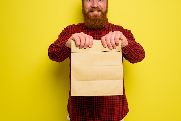 Delivery man with hat and beard has an happy expression