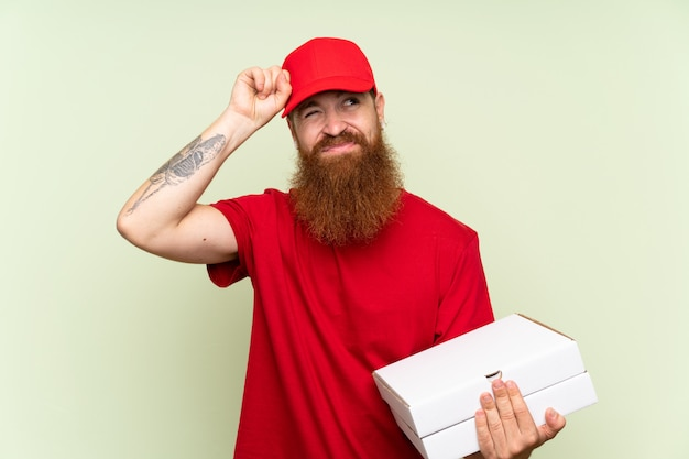 Delivery man with long beard over isolated green background having doubts and with confuse face expression