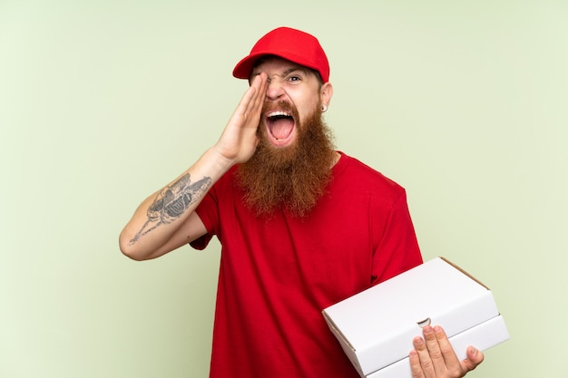 Delivery man with long beard over isolated green background shouting with mouth wide open