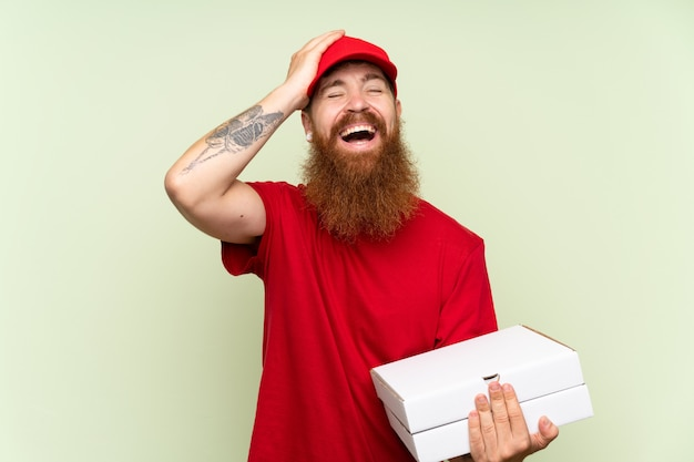 Delivery man with long beard over isolated green wall has realized something and intending the solution
