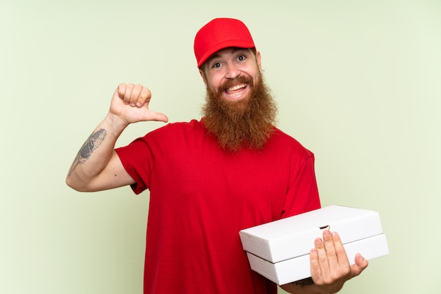 Delivery man with long beard over isolated green wall proud and self satisfied