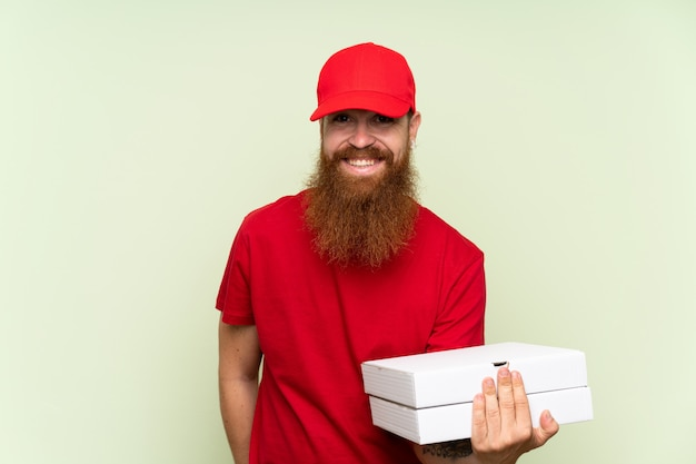 Delivery man with long beard over isolated green wall smiling a lot